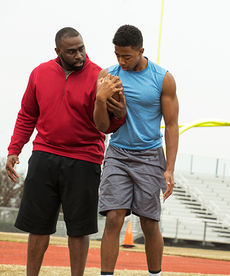 coach helping a student athlete
